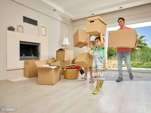 Famille portant grandes boîtes en carton dans la nouvelle maison Portrait