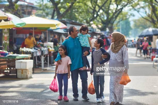 市場を歩いてビニール袋を運ぶ家族 - マレーシア ストックフォトと画像