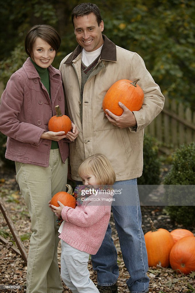 Family carrying pumpkins : Stockfoto