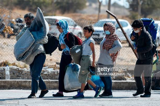 Family carrying their belongings walk toward a new temporary camp, set up to shelter refugees from the burnt Moria refugee camp, on the island of...