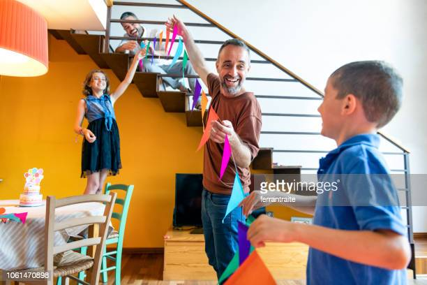 family celebrating a birthday - garland decoration stock pictures, royalty-free photos & images