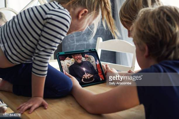 family celebrating a birthday together on a video call - évitement photos et images de collection