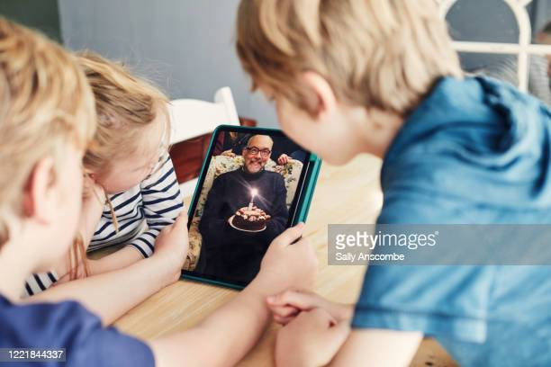 family celebrating a birthday together on a video call - social distancing stock pictures, royalty-free photos & images