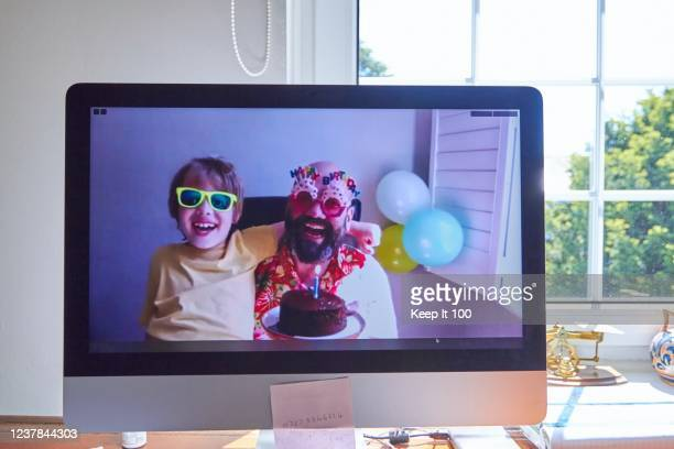 family celebrating a birthday together on a video call - coronavirus photos stock pictures, royalty-free photos & images