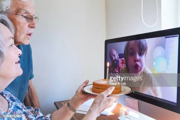 family celebrating a birthday together via video call - life events stock pictures, royalty-free photos & images