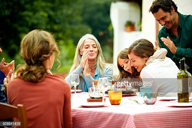Family celebrating birthday at outdoor meal table