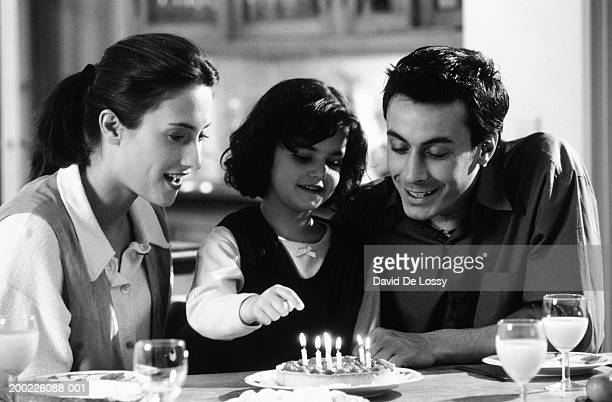family celebrating birthday of daughter (6-7 years), daughter blowing out candle (b&w) - 25 29 years stock pictures, royalty-free photos & images