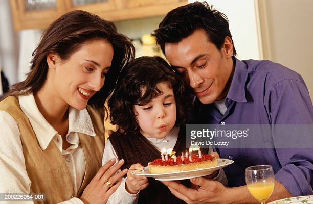 Family celebrating birthday of daughter (6-7years), daughter blowing out candles