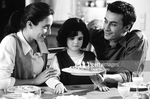 family celebrating birthday of daughter (6-7 years), daughter watching candles (b&w) - 25 29 years stock pictures, royalty-free photos & images
