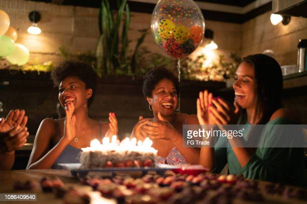 family celebrating birthday party at home - woman birthday stock pictures, royalty-free photos & images