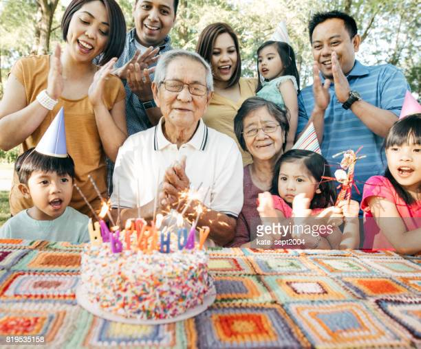 family celebrating birthday together - asian family stock photos and pictures