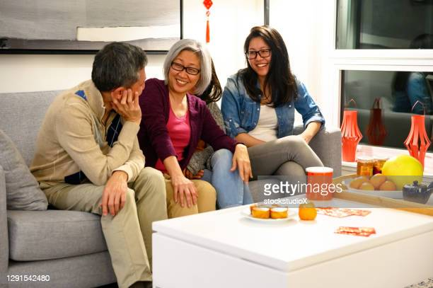 family celebrating chinese new years at home - 25 29 years stock pictures, royalty-free photos & images
