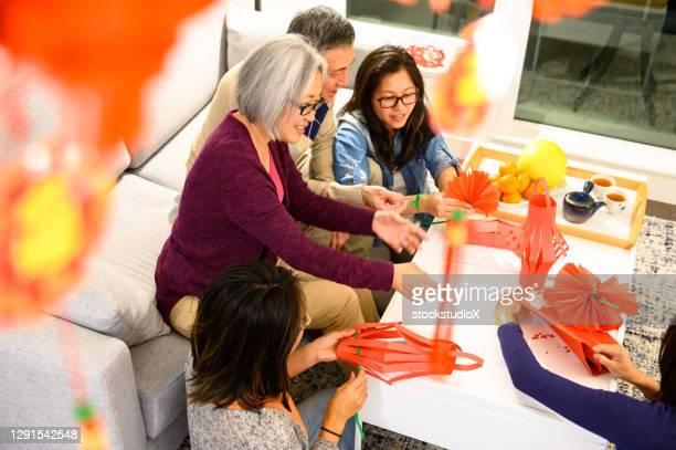 famille célébrant le nouvel an chinois à la maison - 30 34 years photos et images de collection