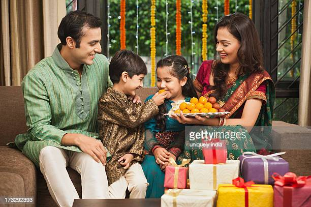 family celebrating diwali - diwali sweets stock photos and pictures