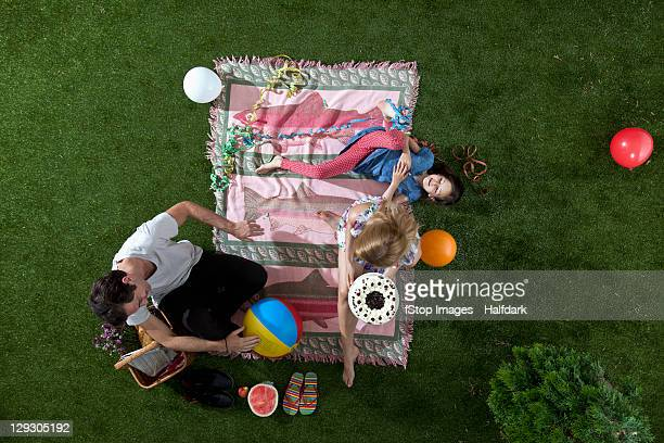 A family celebrating during a picnic in the park with cake, balloons and streamers, overhead view
