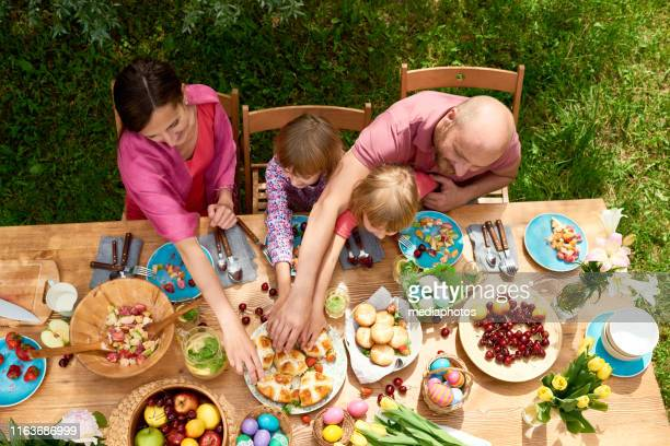 family celebrating easter - easter dinner stock pictures, royalty-free photos & images