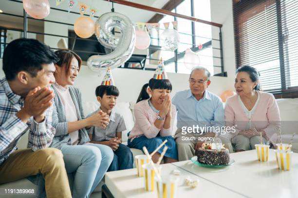 family celebrating girl's birthday - south_agency stock pictures, royalty-free photos & images
