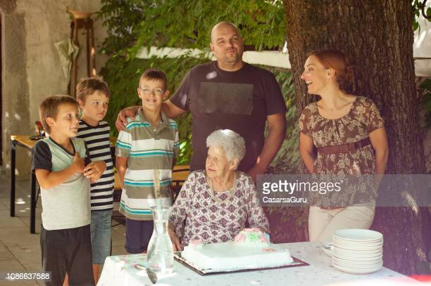 family celebrating grandmothers birthday with birthday cake - 90 plus years stock pictures, royalty-free photos & images