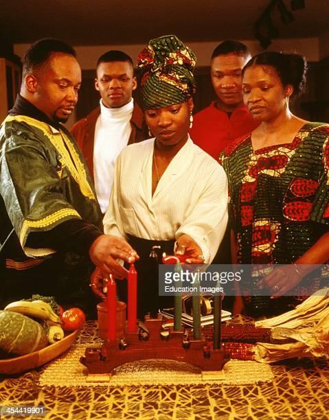 Family Celebrating Kwanzaa Lighting Candles Seven Symbols Of Kwanzaa