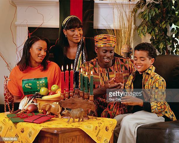 family celebrating kwanzaa - kwanzaa stock pictures, royalty-free photos & images