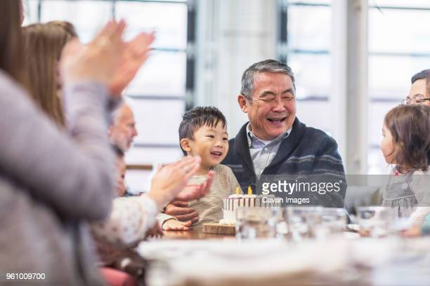family celebrating senior mans birthday in restaurant - life events stock pictures, royalty-free photos & images