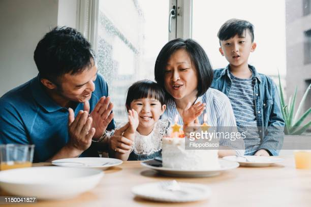 family celebrating the birthday of the little daughter together - chinese ethnicity stock pictures, royalty-free photos & images