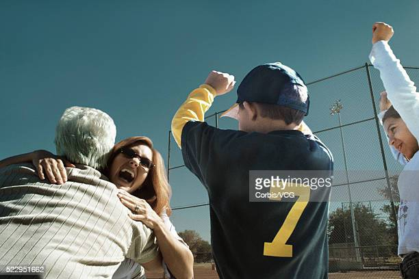 family celebrating victory at baseball game - baseball mom stock pictures, royalty-free photos & images