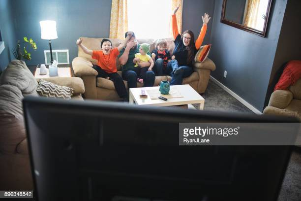 family celebrating while watching football game - family watching tv stock pictures, royalty-free photos & images