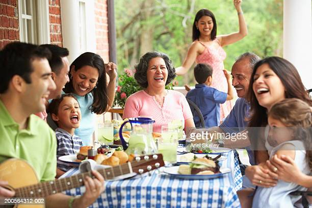 Family celebrating, woman dancing with boy in background