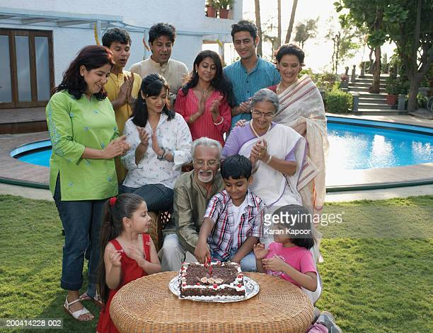 Family celebration in garden, grandfather cutting cake with grandson