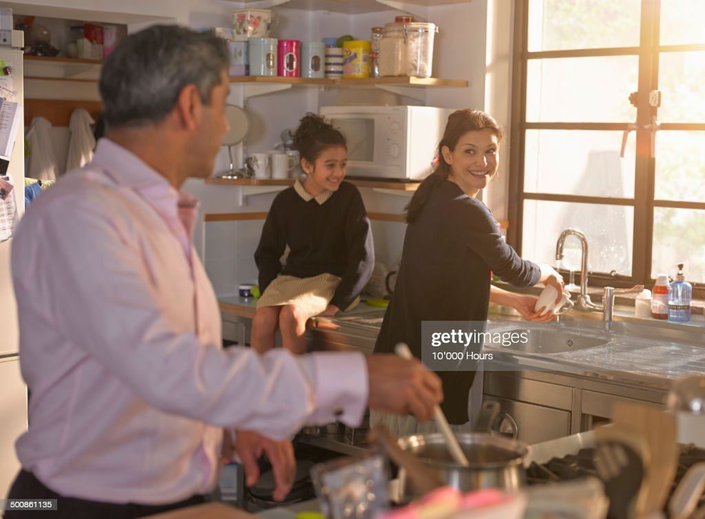Family chatting and cooking an evening meal : Stockfoto