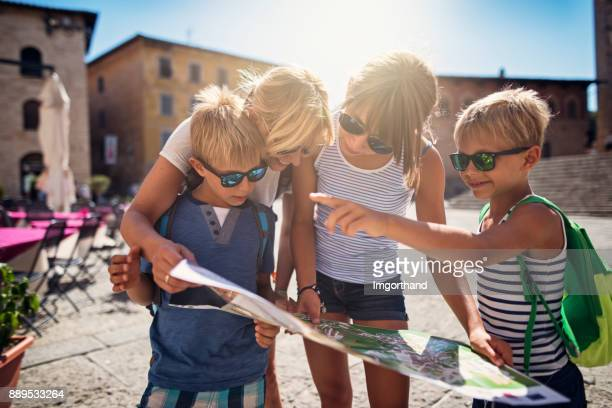 family checking map in italian town of massa marittima in tuscany - tourism stock pictures, royalty-free photos & images