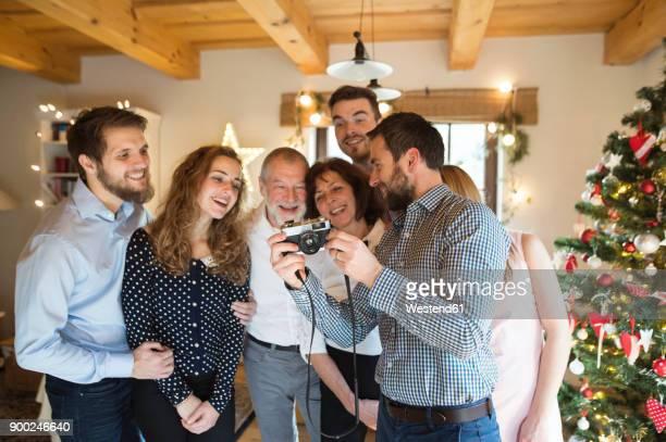 Family checking photos at Christmas tree