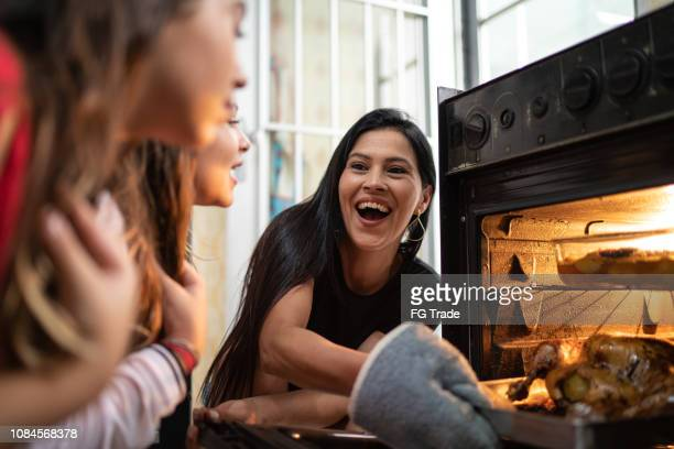family checking the traditional turkey for christmas dinner - spanish and portuguese ethnicity stock pictures, royalty-free photos & images