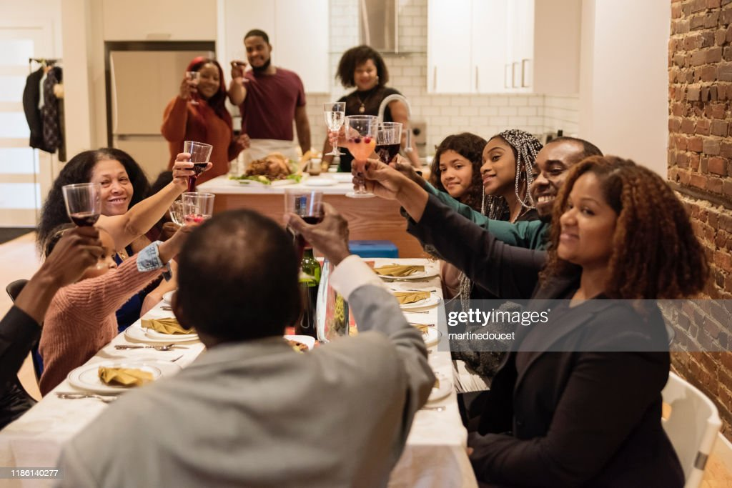 Family cheering enjoying Thanksgiving dinner. : Stock Photo