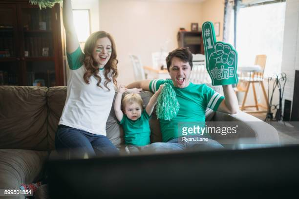 family cheering while watching football game - family watching tv stock pictures, royalty-free photos & images