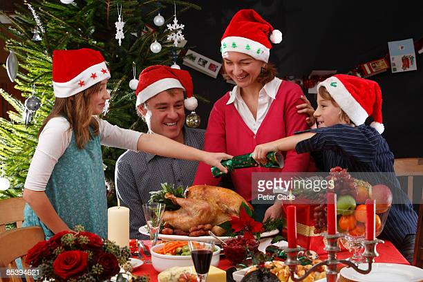 family christmas dinner pulling cracker - four people stock pictures, royalty-free photos & images