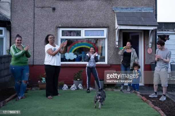 A family claps to show their appreciation for NHS and other key workers on Lawrenny Avenue on April 9 2020 in Cardiff United Kingdom Following the...
