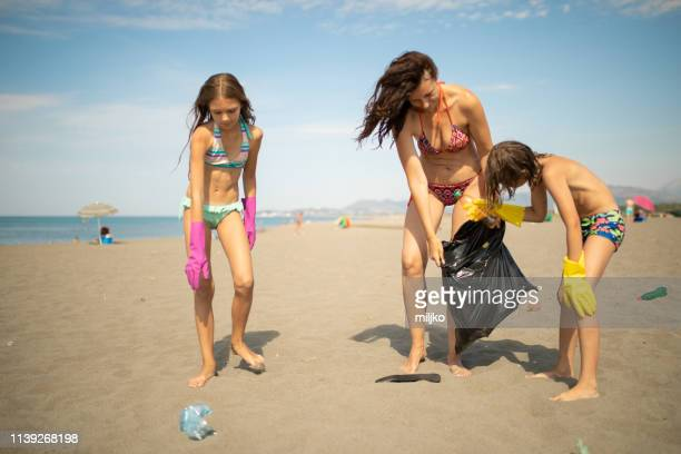 family cleaning beach from plastic waste - green glove stock photos and pictures