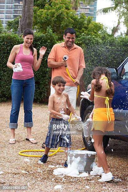 Family cleaning car, father turning hose on daughter (7-9), laughing