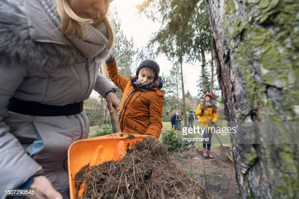 family cleaning up backyard on the early spring day - five people stock pictures, royalty-free photos & images