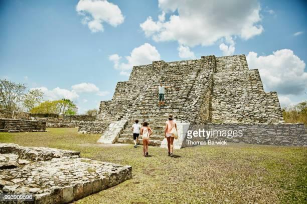 Family climbing Mayan ruins while on vacation
