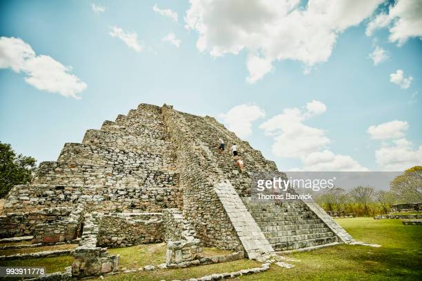 Family climbing pyramid while exploring Mayapan ruins during vacation