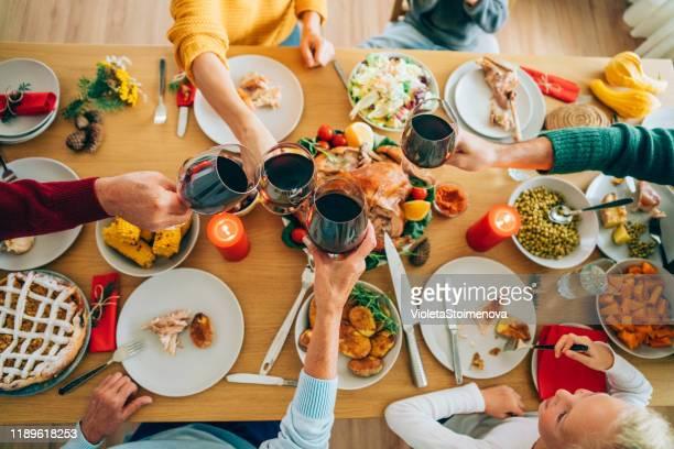 family clinking glasses at christmas dinner. - pessoa irreconhecível imagens e fotografias de stock
