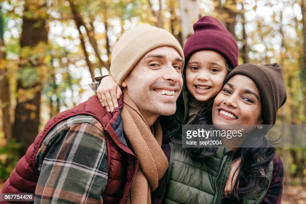 family close up portrait in warm clothes at the park - mixed race person stock pictures, royalty-free photos & images