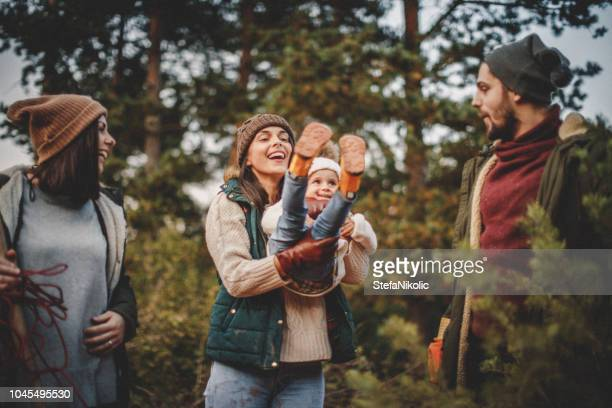 familie sammeln ihre baum für die weihnachtszeit - gummistiefel frau stock-fotos und bilder