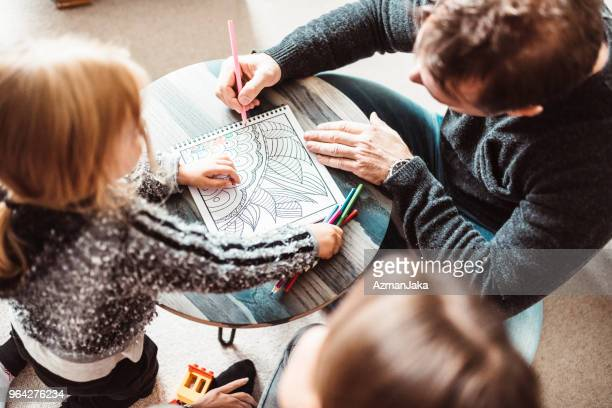 family coloring in the coloring book - colouring book stock photos and pictures