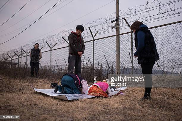 TOPSHOT A family conduct a memorial service for relatives in the North before a barbed wire fence near the Demilitarized Zone separating North and...
