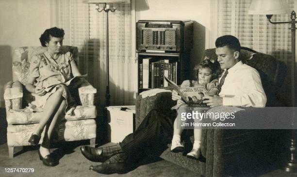 A family consisting of a man woman and child sit in a couple of chairs in a cozy living room and as the man reads to the child a children's book...