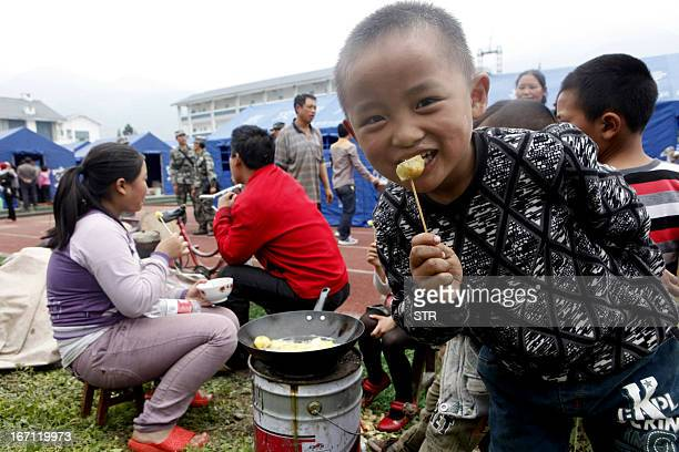 A family cook and eat their dinner outside the makeshift tents housing survivors after an earthquake hit Lushan County in Ya'an City southwest...